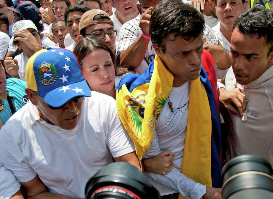 Draped in a Venezuelan national flag, opposition leader Leopoldo Lopez, second from right, is surrounded by anti-government demonstrators and media, just before Lopez surrenders to national guards, in Caracas, Venezuela, Tuesday, Feb 18, 2014. Lopez re-emerged from days of hiding to address an anti-government demonstration and then surrendered to authorities Tuesday in a move that he said will open the world's eyes to the increasingly authoritarian bent of Venezuela's socialist government. Photo: Juan Manuel Hernandez, AP / AP