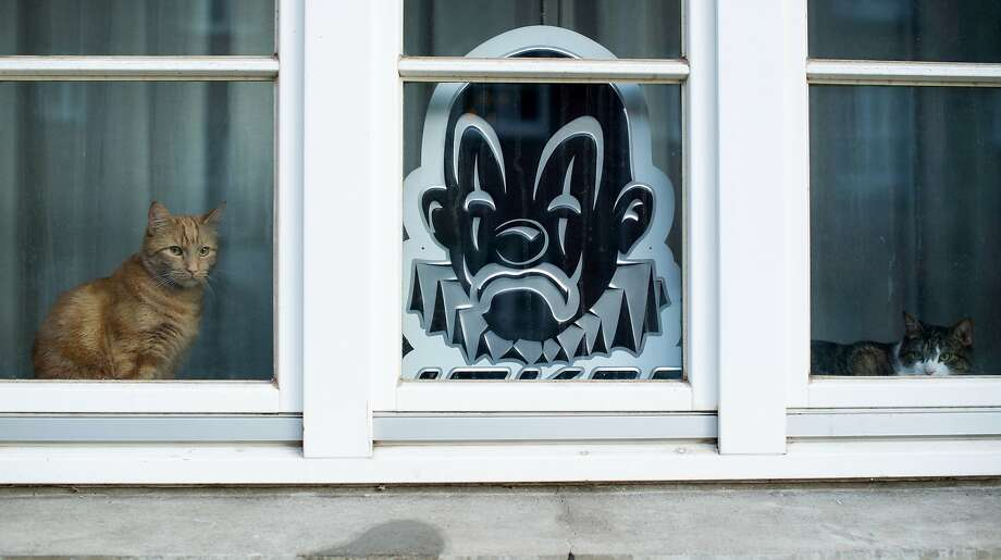 "Window sentinels: As intruders are unlikely to be frightened away by a ""beware of cats"" sign, a homeowner in Hamburg, Germany, opted instead for the ominous angry clown's head. Photo: Maja Hitij, Associated Press"