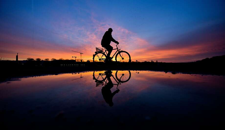 Pedaling in a puddle: Standing water on roadway reflects both cyclist and sunset in Hannover, Germany. Photo: Julian Stratenschulte, Associated Press