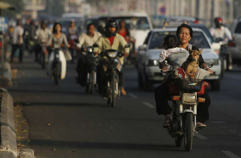 Cambodian soccer mom:In Phnom Penh, a mother chauffeurs her daughter and dog by   motorcycle. Photo: Heng Sinith, Associated Press