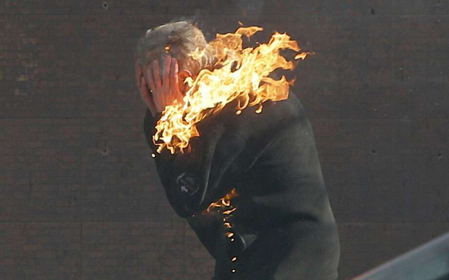 An anti-government protester is engulfed in flames during clashes with riot police outside Ukraine's parliament in Kiev, Ukraine, Tuesday, Feb. 18, 2014. Thousands of angry anti-government protesters clashed with police in a new eruption of violence following new maneuvering by Russia and the European Union to gain influence over this former Soviet republic. (AP Photo/Efrem Lukatsky) Photo: Efrem Lukatsky, Associated Press