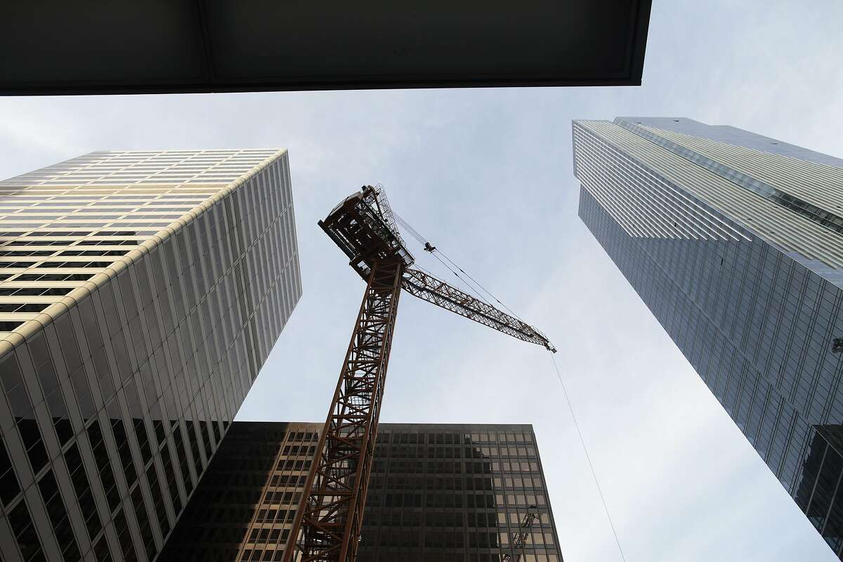 A crane towers over a construction site at 350 Mission St. in San Francisco, Calif. on Thursday, Feb. 13, 2014. The area around First and Mission St. has undergone major physical changes recently with the construction of various towers.