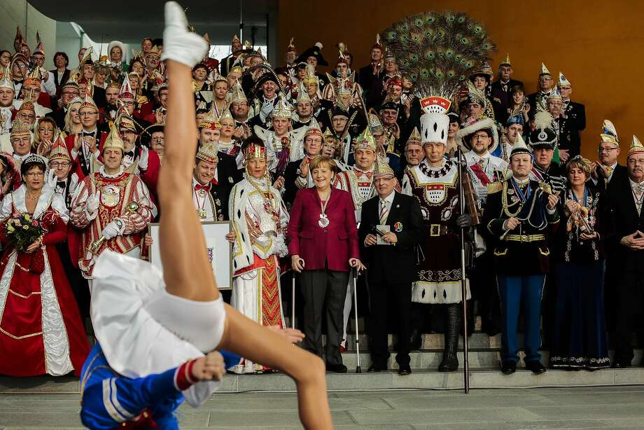 Carnival season kicks off:German Chancellor Angela Merkel, on crutches after a skiing accident, watches a carnival dancer perform during a reception for carnival clubs from all over Germany at the chancellery in Berlin. Photo: Markus Schreiber, Associated Press