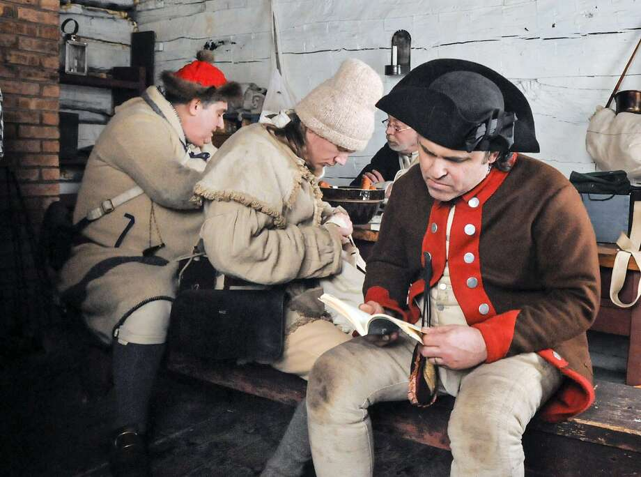 "Wish I had my Kindle:Historical re-enactor Terry Sorchy reads a paperback book, which hasn't been invented yet, during the ""Living History 1775-81: A Winter Garrison"" event in Fort Wayne, Ind. Photo: Michelle Davies, Associated Press"