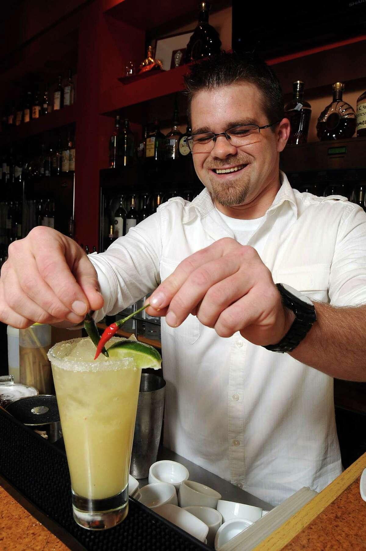 General manager Danny Thurman garnishes a Spicy Ginger Margarita at Rattan Pan Asian Bistro at 1396 Eldridge Parkway Friday Feb 14, 2014.(Dave Rossman photo)