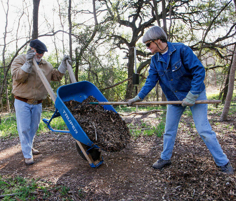 Volunteers Weir Labatt, left, and Charlotte Wenger spread mulch made from Ligustrum and Chinese tallow on walking trails at the Headwaters at Incarnate Word sanctuary Feb. 12. Photo: Photos By Marvin Pfeiffer / Alamo Heights Weekly / Express-News 2014