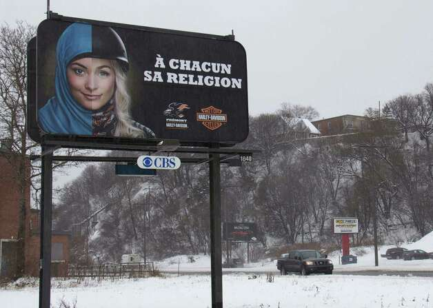 "A billboard in Quebec reading ""To each his own religion,"" shows the face of a young woman wearing on the left half of the face a hijab and the other half face a helmet and a motorcycle jacket. The ad is part of a campaign by a Harley-Davidson motorcycle dealer based on the Quebec Charter of Values. ORG XMIT: MER2014021717154946 Photo: ANNE LEVASSEUR / AFP"
