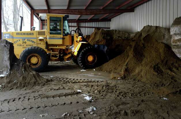 Mark Matto fills his bucket loader with a mixture of sand and salt Tuesday, Feb. 15, 2014, at the Public Works Department in Derby, Conn. as plow trucks come to the yard to be filled. Photo: Autumn Driscoll / Connecticut Post