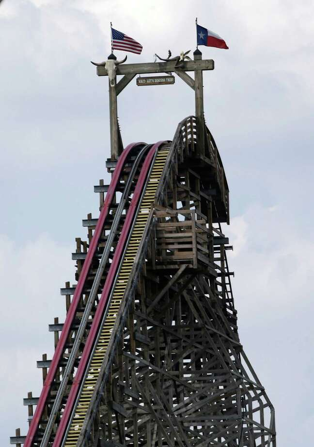 The Texas Giant roller coaster ride sits idle at the Six Flags Over Texas park Saturday, July 20, 2013, in Arlington, Texas. Investigators will try to determine if a woman who died while riding the roller coaster at the amusement park Friday night fell from the ride after some witnesses said she wasn't properly secured.(AP Photo/LM Otero ) Photo: LM Otero, STF / AP