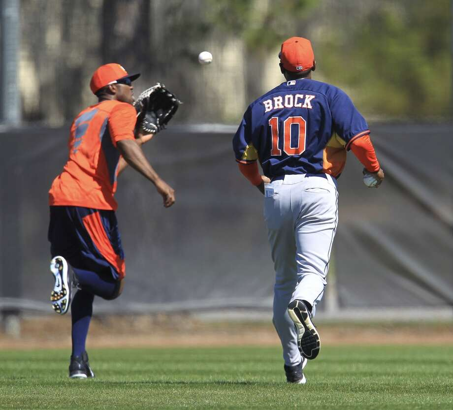 Astros first base coach Tarrik Brock (10) does one-on-one drills Dexter Fowler during workouts for early-arriving position players. Photo: Karen Warren, Houston Chronicle