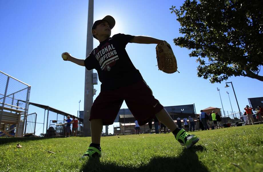 Rocco Arnone, 7, of Boca Raton, plays catch with his dad, Sal, during pitcher and catcher workouts. Photo: Karen Warren, Houston Chronicle
