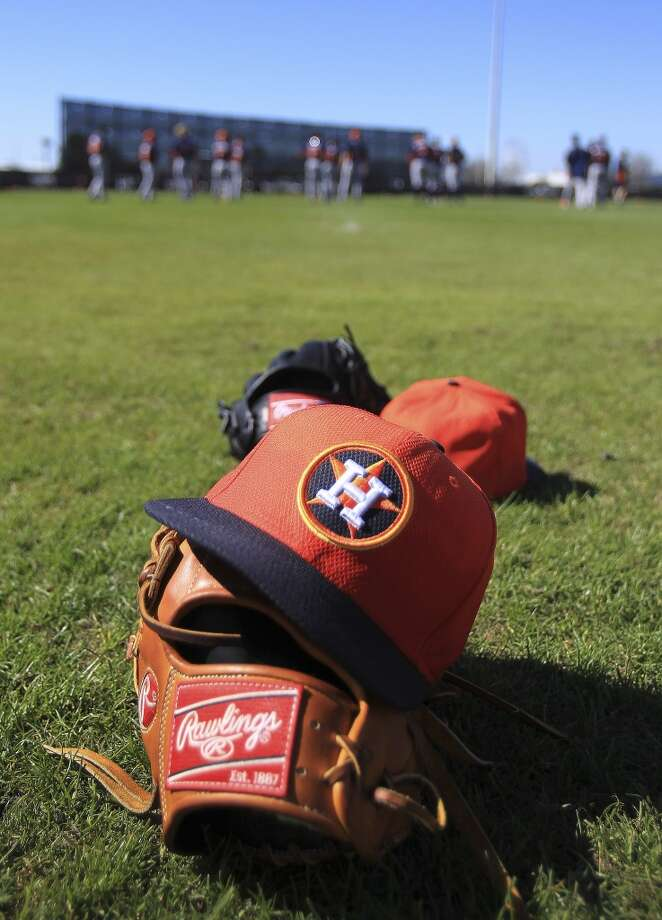 An Astros players' glove and hat sit on the field during pitcher and catcher conditioning drills. Photo: Karen Warren, Houston Chronicle