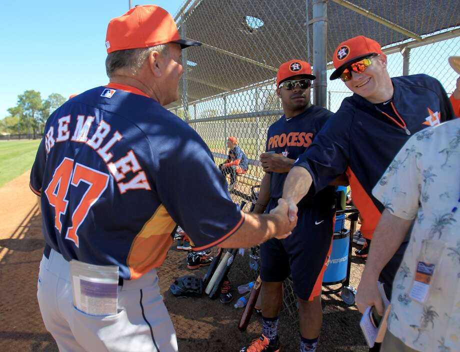 Astros bench coach Dave Trembley shakes hands with Robbie Grossman during workouts for early-arriving position players. Photo: Karen Warren, Houston Chronicle