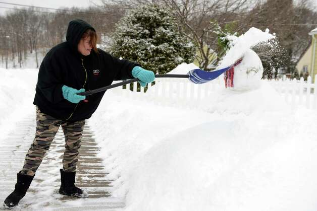 Holly Orazietti shovels the sidewalk in front of her house Tuesday, Feb. 15, 2014 in Derby, Conn. Photo: Autumn Driscoll / Connecticut Post