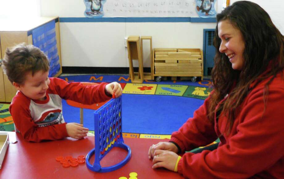 Erin Hanrahan, a teacher in the after-school program at the Fairfield YMCA plays a game with Evan Marshall, 7, a Riverfield School student in the Y's Fun Day program. The Fun Day program meets when Fairfield Schools are closed for snow days. Photo: Staff Photo/Gretchen Webster / Fairfield Citizen