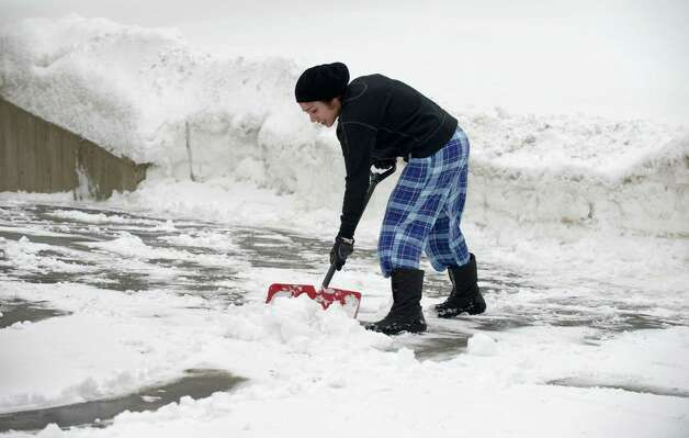 Preet Kaur, age 25, of Bethel, Conn, was shoveling snow off her driveway with her sisters on Tuesday afternoon, February 18, 2014. Photo: H John Voorhees III / The News-Times Freelance