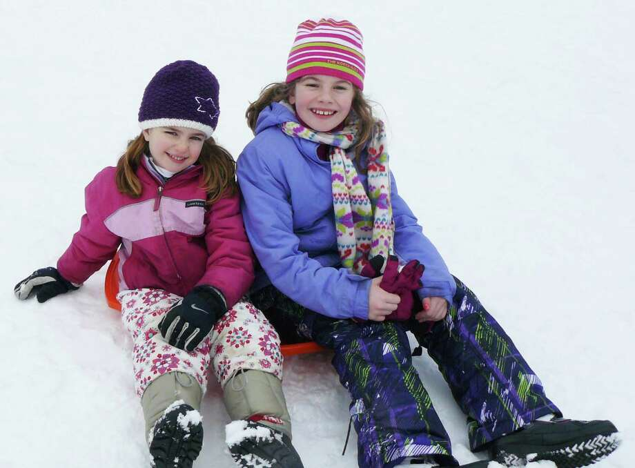 North Stratfield School kindergartner Grace Ronaan, 5, and her sister Maeve, 9, a third grader, get ready to launch down the hill at Fairfield University on Tuesday - Fairfield Schools' fifth snow day this year. Photo: Staff Photo/Gretchen Webster / Fairfield Citizen
