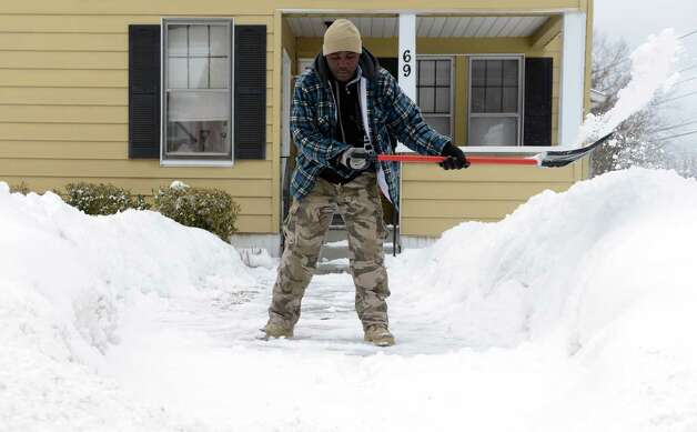 Felix Lupenga shovels the walkway in front of his house Tuesday, Feb. 15, 2014 in Derby, Conn. Photo: Autumn Driscoll / Connecticut Post