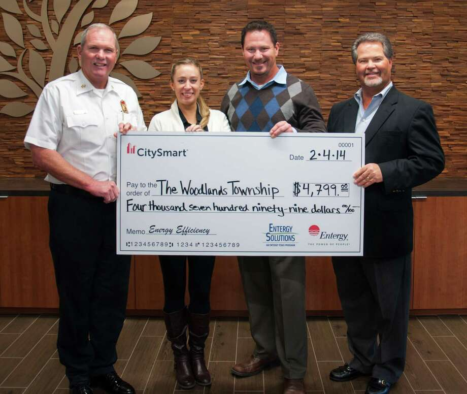 From left, Alan Benson, Megan Frisa, Phil Lanier and John Powers show a check from Entergy Texas to The Woodlands Township. Photo: Provided By The Woodlands Township / The Woodlands Township