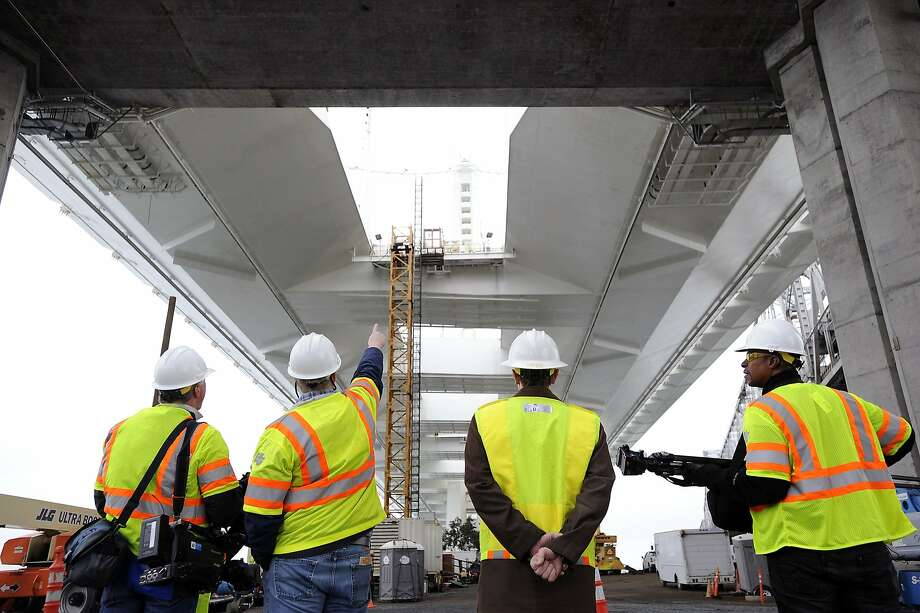 Members of the media gather underneath the Eastern span of the Bay Bridge in Oakland, CA Monday, February 10, 2014, in order to take a tour of the newly found leaks under the roadway. Photo: Michael Short, Special To The Chronicle