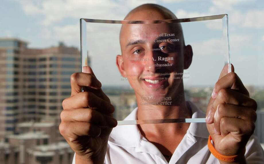 James Ragan holds an etched glass piece by appointing him as a special ambassador of MD Anderson at the Pickes Academic Tower Wednesday, Aug. 29, 2012, in Houston. Dr. Ron DePinho recognized Ragan because of his efforts to raise awareness of the need for pediatric cancer research support. Photo: Cody Duty, Houston Chronicle / © 2011 Houston Chronicle