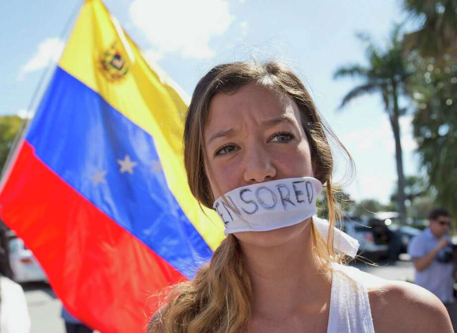 "Valentina Pilonieta Vera, 23, wears a gag over her mouth with the word ""Censored"" written on it, as she attends a demonstration, Tuesday, Feb. 18, 2014 in Doral, Fla. Dozens of Venezuelans gathered near a street corner to show their support for Venezuelan opposition leader Leopoldo López and the university students that have been carrying out street protests in that South American country. Photo: Wilfredo Lee, AP / AP"