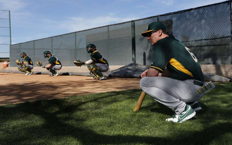 A's manager Bob Melvin with catchers behind, watches  as pitchers throw at the Papago Baseball Facility in Phoenix, Arizona on Tuesday Feb. 18,  2014. Major League Baseball's Oakland Athletics continue their spring training in the Arizona Desert in preparation for the upcoming season. Photo: The Chronicle