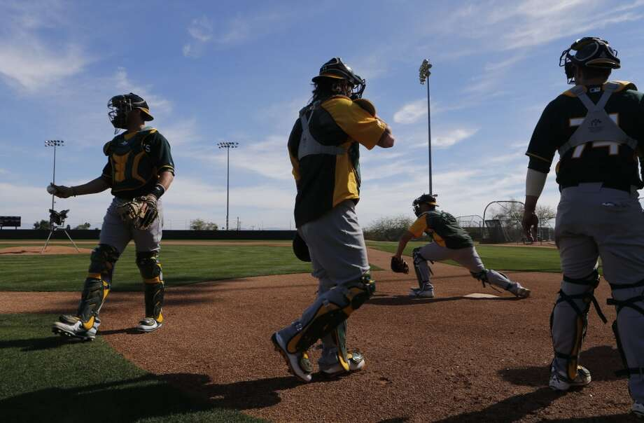 A's catchers during practice drills at the Papago Baseball Facility in Phoenix, Arizona on Tuesday Feb. 18,  2014. Major League Baseball's Oakland Athletics continue their spring training in the Arizona Desert in preparation for the upcoming season. Photo: The Chronicle