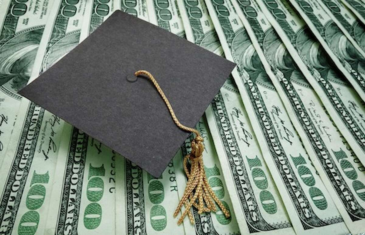 graduation cap on assorted hundred dollar bills - education concept