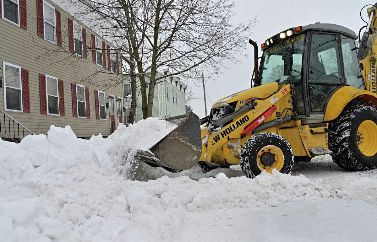 City crews use heavy equipment to clear snow along 110th Street Tuesday Feb. 18, 2014, in Troy, NY. (John Carl D'Annibale / Times Union)