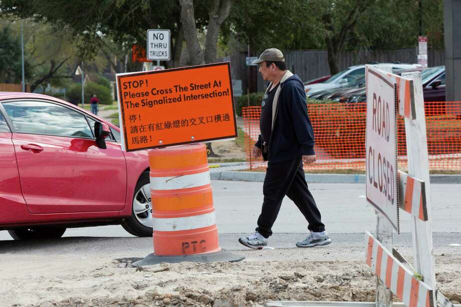 A pedestrian crosses Bellaire Boulevard, ignoring the sign discouraging people from jaywalking. Photo: Marie D. De Jeséºs, Staff / © 2014 Houston Chronicle