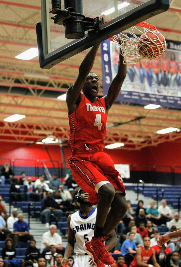 Travis'  Hakeem Butler dunks past Clear Spring's Cory Smith (5) during a high school basketball playoff game between Travis and Clear Springs Tuesday, Feb. 18, 2014. Photo: Bob Levey / ©2014 Bob Levey