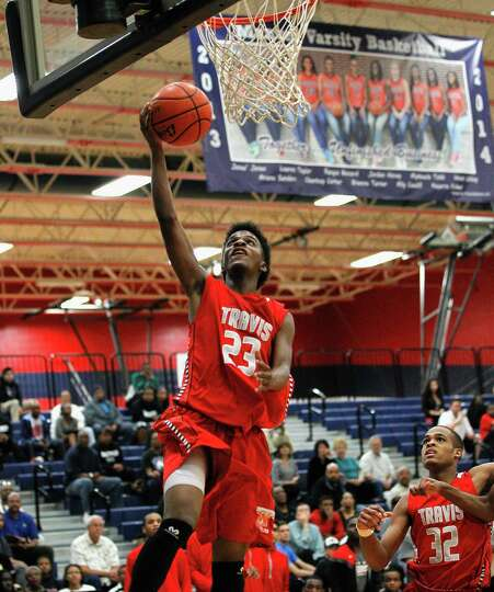 Travis' robert Johnson drives to the basket for a layup against Clear Springs during a high school b