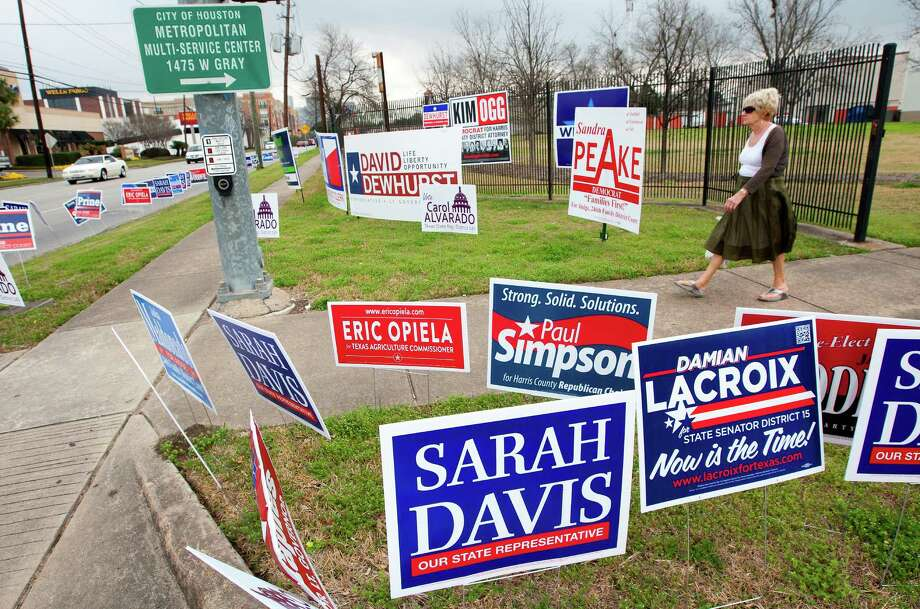 Lynda Cooke confronts a landscape awash in political signs Tuesday at the Houston Metropolitan Multi-Service Center, one of 39 locations in Harris County where early ballots can be cast through Feb. 28. The deadline to request a mail-in ballot is Friday. Photo: Cody Duty, Staff / © 2014 Houston Chronicle