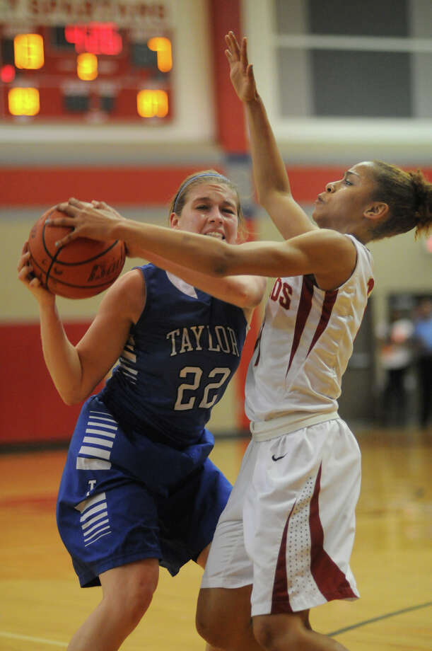 Cy-Woods junior guard Tatyana Perez, right, puts the defensive pressure on Katy Taylor senior guard Cailin Scherpereel during their Region III-5A quarterfinal matchup Cy-Lakes High School on Tuesday. Photo: Jerry Baker, For The Chronicle