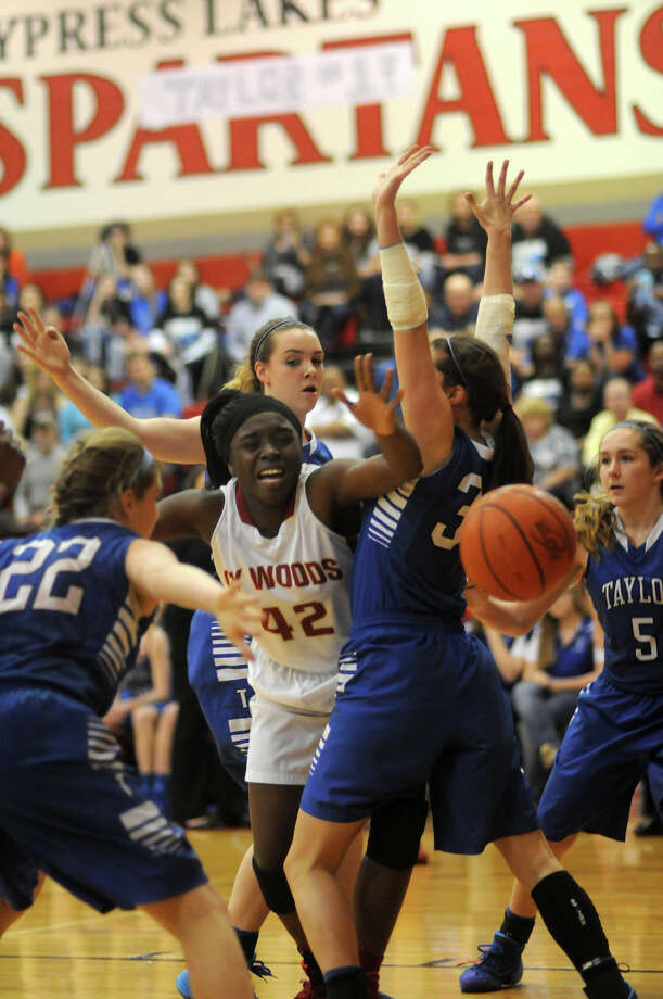 Cy-Woods senior forward Olivia Ogwumike (#42) gets the quadruple team defense from Katy Taylor's Cailin Scherpereel, from left, Samantha Saccomen, Emily Williams, and Tarin Scherpereel during 1st quarter action of their Region III-5A quarterfinal matchup Cy-Lakes High School on Tuesday. Photo: Jerry Baker, For The Chronicle