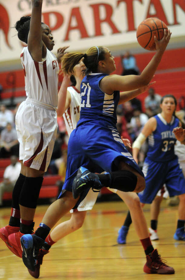 Katy Taylor junior guard Samantha Atkinson-Roach, from right, drives to the hoop against Cy-Woods junior guard Erica Okwumike during 2nd quarter action of their Region III-5A quarterfinal matchup Cy-Lakes High School on Tuesday. Photo: Jerry Baker, For The Chronicle