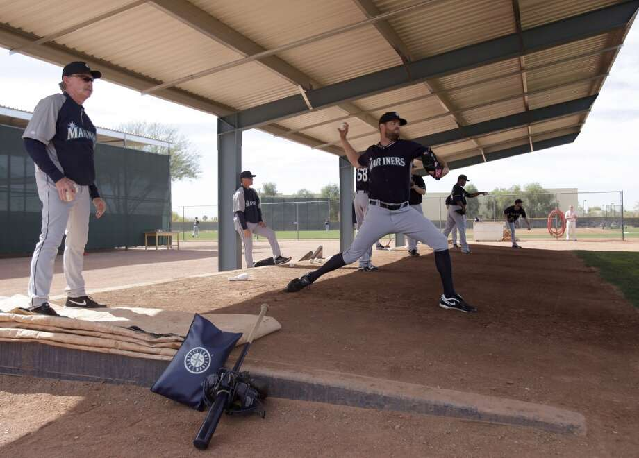 Seattle Mariners pitchers throw out of the bullpen during spring training baseball practice, Tuesday, Feb. 18, 2014, in Peoria, Ariz. (AP Photo/Rick Scuteri) Photo: AP