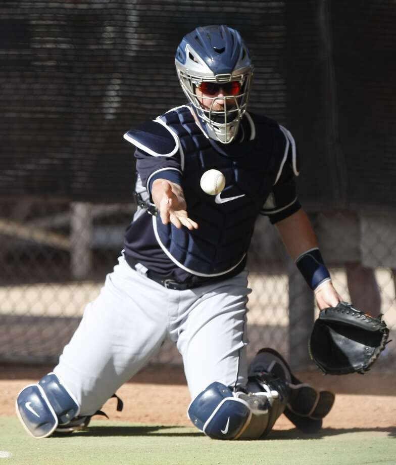 Seattle Mariners catcher John Buck (4) flips the ball during spring training baseball practice, Tuesday, Feb. 18, 2014, in Peoria, Ariz. (AP Photo/Rick Scuteri) Photo: AP