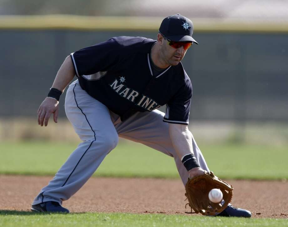 Seattle Mariners infielder Willie Bloomquist (8) shags balls during spring training baseball practice, Tuesday, Feb. 18, 2014, in Peoria, Ariz. (AP Photo/Rick Scuteri) Photo: AP