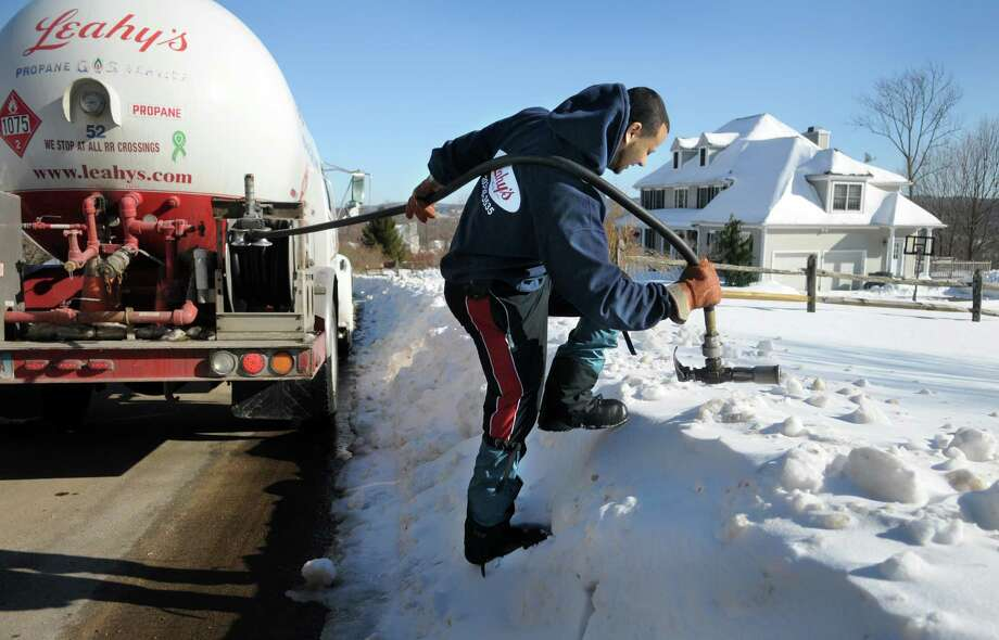 Yeuri Espinal, 30, of Danbury, Conn., with Leahy's,  delivers propane fuel to a home in Danbury, Conn., Monday, Feb. 17, 2014. Photo: Carol Kaliff / The News-Times