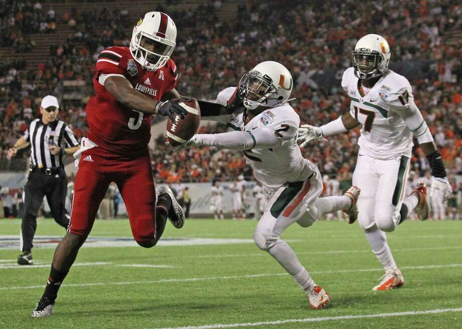 Louisville's Teddy Bridgewater, left, is the top-rated quarterback in the upcoming draft, according to NFL Network analyst Mike Mayock. Photo: AL DIAZ, MBR / Miami Herald