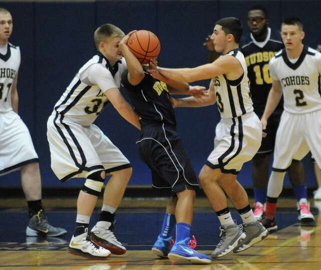 Cohoes plays tight defence on Hudson's Gerell Young during their Class B sectional boy's basketball