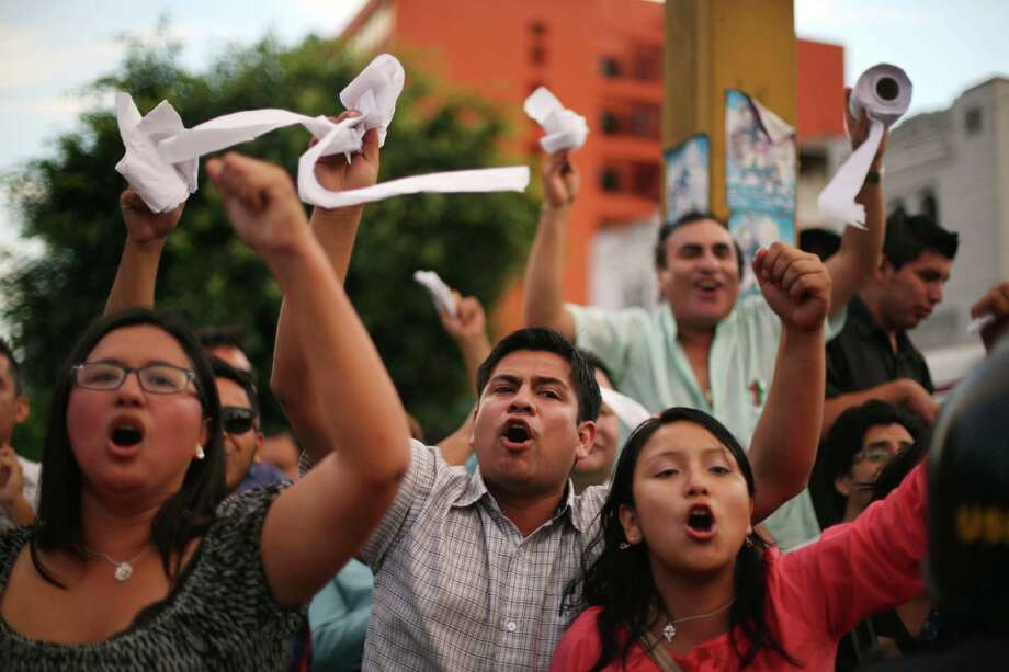 Demonstrators hold up toilet paper and shout slogans against Venezuela's President Nicolas Maduro outside Venezuela's embassy in Lima, Peru, Tuesday, Feb. 18, 2014. Hundreds of students have spent the past week in the streets of Caracas, Venezuela alternating between peaceful protests by day and pitched battles with police at night in unrest fed by hardships that include rampant crime, more than 50 percent inflation and shortages of basic goods  like toilet paper. Photo: Martin Mejia, AP / AP