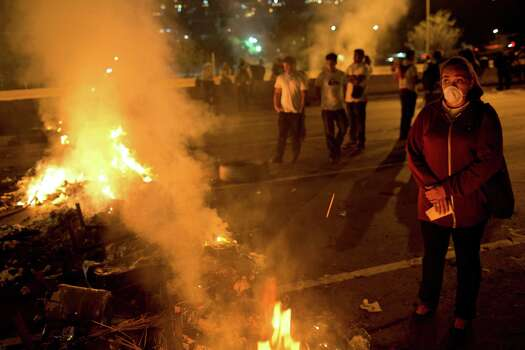 A demonstrator stands next to a burning barricade during an opposition protest outside La Carlota airport in Caracas, Venezuela, Tuesday, Feb. 18, 2014. Members of the opposition are protesting after their leader Leopoldo Lopez surrendered to authorities Tuesday. Lopez was being sought by authorities for allegedly inciting violence during protests last week in which three people were killed as government forces clashed with protesters. Photo: Rodrigo Abd, AP / AP