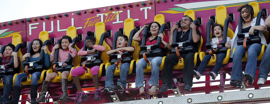 Taking advantage of mild weather Friday, riders try the Full Tilt at the Wade Shows carnival. The carnival includes Li'L Partner Land, an area specifically for parents with young children. Photo: Edward A. Ornelas / San Antonio Express-News / © 2014 San Antonio Express-News