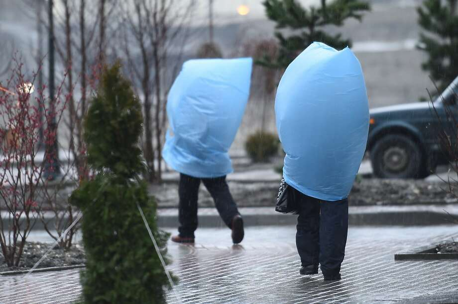 TOPSHOTS Workers protect themselves from heavy rain as they walk to the media center during the Sochi Winter Olympics on February 18, 2014.      AFP PHOTO / LEON NEALLEON NEAL/AFP/Getty Images Photo: Leon Neal, AFP/Getty Images