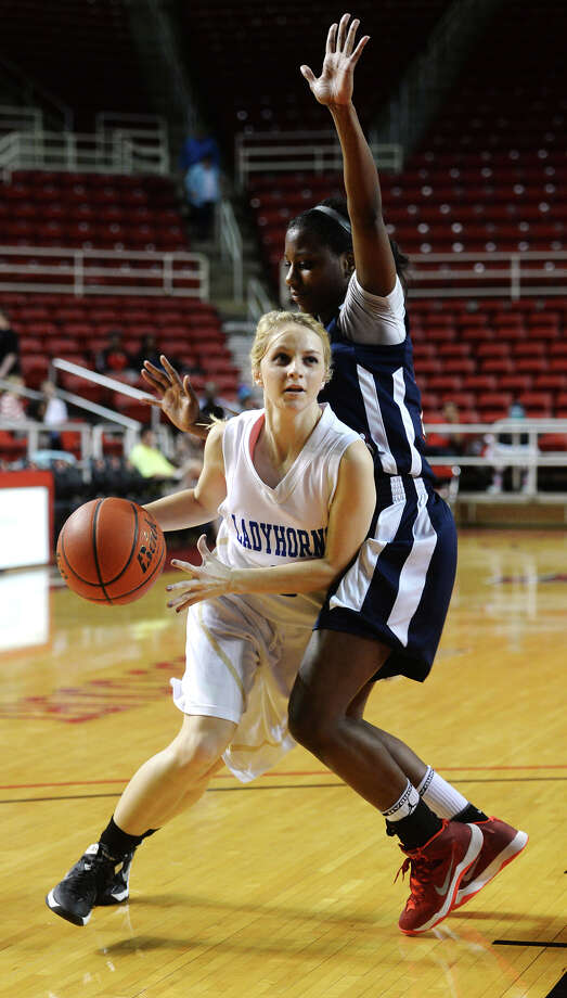 Hamshire-Fannett's Hannah Hulet, No. 0, slips around Hardin-Jefferson's Kesha Broussard, No. 14, on Tuesday night. The Hardin-Jefferson and Hamshire-Fannett girls basketball teams went head-to-head in playoffs at the Montagne Center on Tuesday night. Photo taken Tuesday, 2/18/14 Jake Daniels/@JakeD_in_SETX Photo: Jake Daniels / ©2013 The Beaumont Enterprise/Jake Daniels