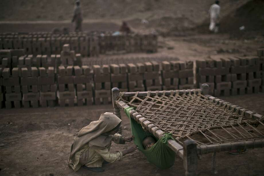 Pakistani girl, Kiran Riasat, 8, who works with her mother and father, seen in the background, in a brick factory, checks on her brother, Rizwan, 1.5, laying in a hammock attached on a bed, at the site of work, in the outskirts of Islamabad, Pakistan, Tuesday, Feb. 18, 2014. According to Kiran's parents she started to work at the factory 3 years ago, and they couldn't afford financially sending her to a school. (AP Photo/Muhammed Muheisen) Photo: Muhammed Muheisen, Associated Press