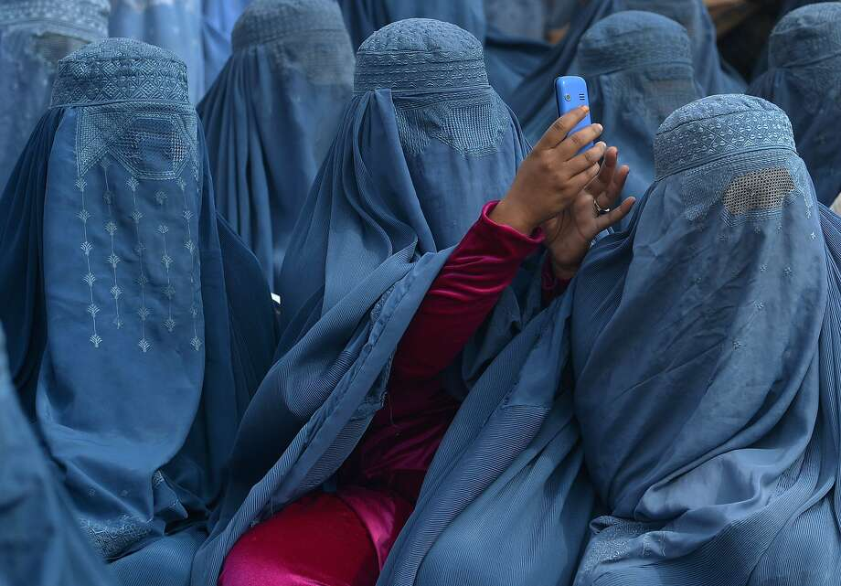 Big smile, everyone!A woman takes a photograph during an election rally for presidential candidate Abdullah Abdullah in Jalalabad, Afghanistan. Photo: Shan Marai, AFP/Getty Images